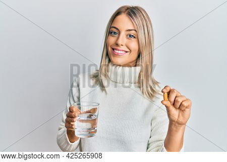 Beautiful blonde woman holding pill and glass of water smiling with a happy and cool smile on face. showing teeth.
