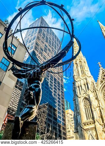 A rear, diagonal shot of the Atlas statue next to an office skyscraper and St. Patrick\'s Cathedral near by, under a partly cloudy blue sky on a sunny day.  6/29/2021