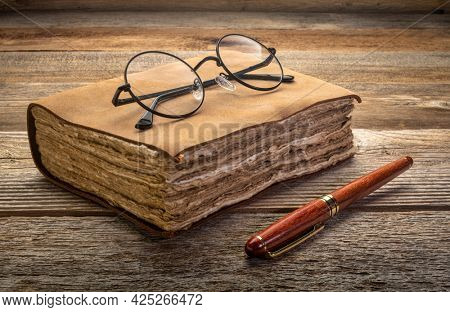 antique leatherbound journal with decked edge handmade paper pages and a stylish pen and reading glasses on a rustic wooden table, journaling concept