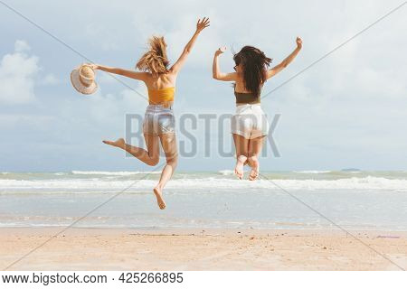 Two Asian Women In Summer Casual Clothes Jumping On The Beach Having Fun. Young Female Friends Weari