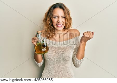 Young caucasian woman holding olive oil can screaming proud, celebrating victory and success very excited with raised arm