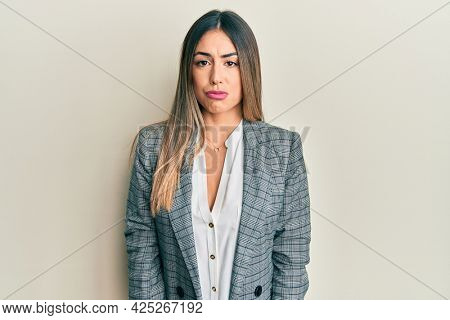 Young hispanic woman wearing business clothes depressed and worry for distress, crying angry and afraid. sad expression.