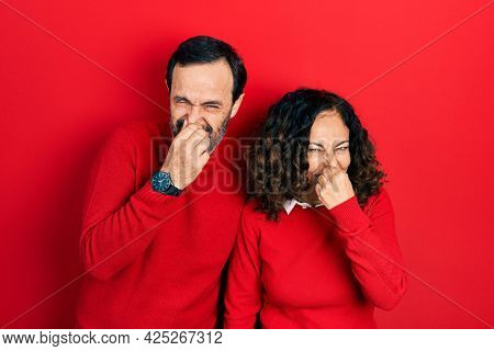 Middle age couple of hispanic woman and man hugging and standing together smelling something stinky and disgusting, intolerable smell, holding breath with fingers on nose. bad smell