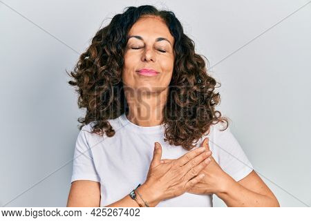 Middle age hispanic woman wearing casual white t shirt smiling with hands on chest, eyes closed with grateful gesture on face. health concept.