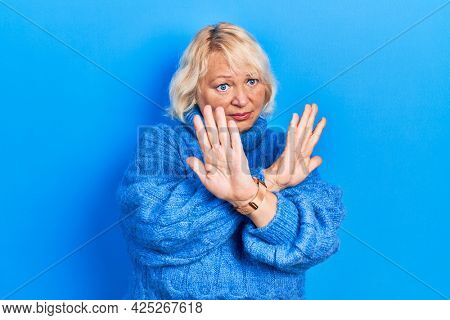 Middle age blonde woman wearing casual clothes rejection expression crossing arms doing negative sign, angry face