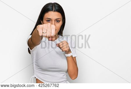 Young hispanic girl wearing casual white t shirt punching fist to fight, aggressive and angry attack, threat and violence