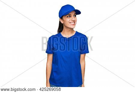 Young hispanic girl wearing delivery courier uniform looking away to side with smile on face, natural expression. laughing confident.