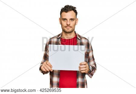 Young hispanic man holding blank empty banner thinking attitude and sober expression looking self confident
