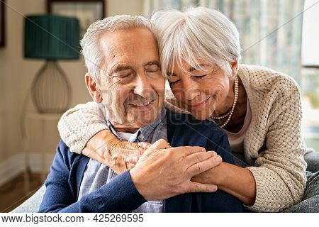 Romantic senior woman embracing from behind her husband sitting on sofa. Cute old couple in love hugging with closed eyes. Retired woman consoling her husband at home.