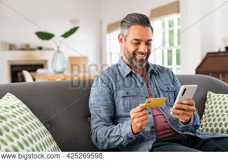 Middle eastern mature man using credit card to make online payment on smartphone. Mixed race man using cellphone for shopping online. Guy using smart phone to check credit card transactions from app.