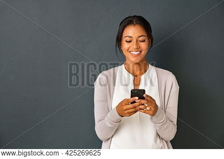 Mid adult african american woman texting message on smart phone isolated on grey background. Smiling indian woman using mobile phone. Happy multiethnic lady messaging on the smartphone with new app.