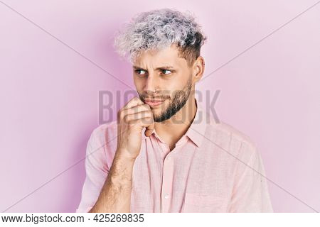 Young hispanic man with modern dyed hair wearing casual pink shirt thinking concentrated about doubt with finger on chin and looking up wondering