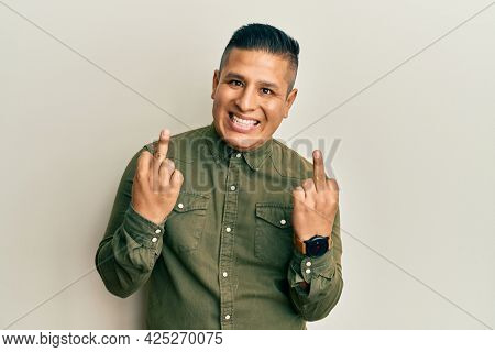 Young latin man wearing casual clothes showing middle finger doing  bad expression, provocation and rude attitude. screaming excited