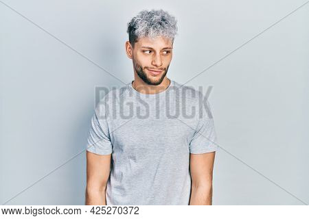 Young hispanic man with modern dyed hair wearing casual grey t shirt smiling looking to the side and staring away thinking.
