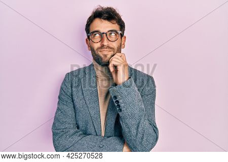 Handsome man with beard wearing business jacket and glasses thinking concentrated about doubt with finger on chin and looking up wondering