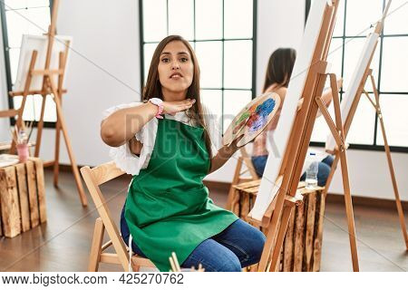 Young hispanic artist women painting on canvas at art studio cutting throat with hand as knife, threaten aggression with furious violence