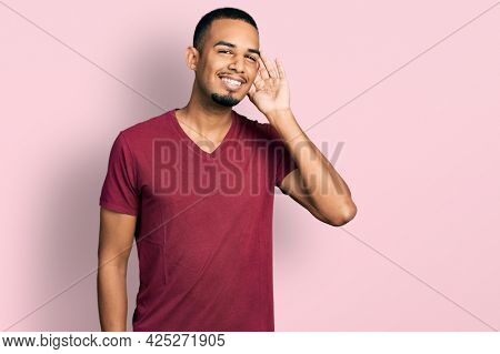 Young african american man wearing casual t shirt smiling with hand over ear listening and hearing to rumor or gossip. deafness concept.