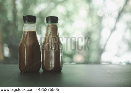 Two Bottle Of Coffee Mocha Against Nature Background.