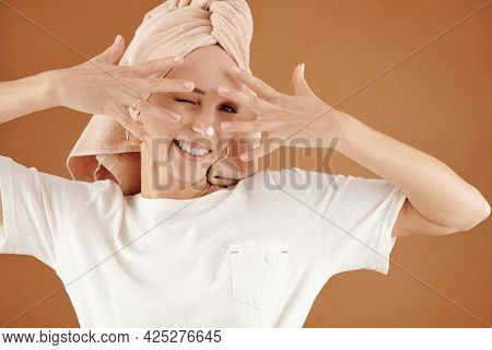 Portrait Of Smiling Playful Young Caucasian Woman With Hair Wrapped Into Towel Keeping Fingers Sprea