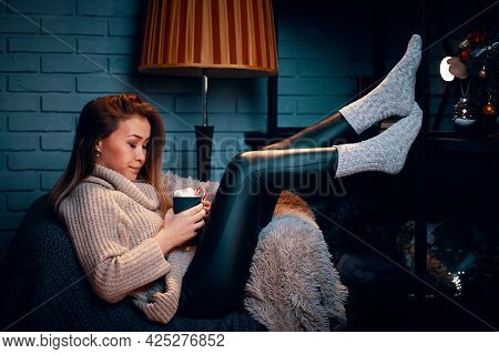 Serious Girl In Sweater On Chair. Mug Of Hot Chocolate With Marshmallows. Striped Floor Lamp. Gray B