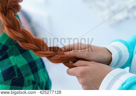 A Friend Is Braiding A Braid For A Red-haired Girl. Hairstyle For A Cute Young Woman