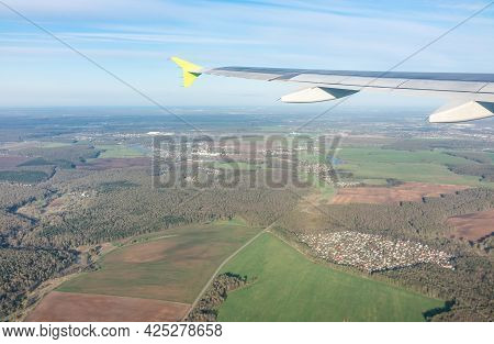 View Of Airplane Wing, Blue Skies And The Land During Landing In Moscow, Russia. Airplane Window Vie