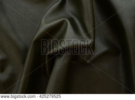 Dark Background Leather Fabric Khaki Color, Fabric Folds.