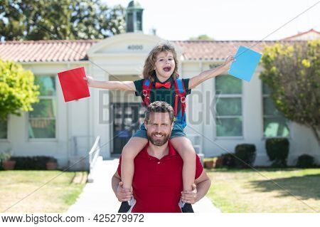 Excited Father Piggyback Ride Son To School. Parent And Pupil Of Primary School Schoolboy With Backp
