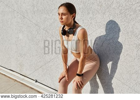 Sporty Woman With Perfect Body Wearing White Top And Beige Leggins, Posing Leaning To Grey Wall Outd