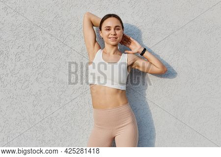 Outdoor Shot Of Happy Female Of Young Age Wearing White Top And Beige Leggins, Raising Arms, Looking