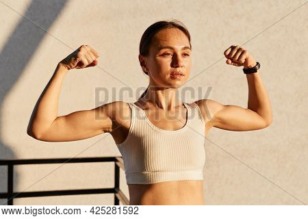 Outdoor Shot Of Young Female Athlete Flexing Muscles, Showing Strong Arm Biceps, Healthy Body, Produ