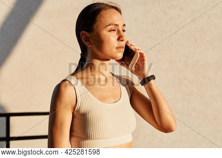 Young Brunette Sporty Girl Talking On The Smartphone Near The Gray Wall, Wearing White Sporty Top, L