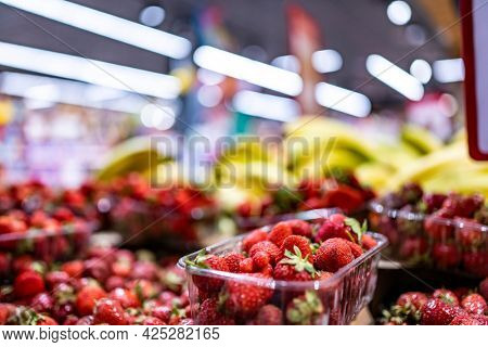 Colorful fruits and berries on farmer market shop. Bananas and strawberry sold at grocery bazaar supermarket. Various healthy local and exotic food