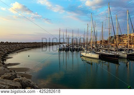 Marina is a specially equipped harbor for yachts, boats and small boats in Herzliya, Israel. Evening twilight on the Mediterranean Sea. Walk along the breakwater