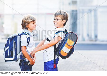 Two Little Kid Boys With Satchels. Schoolkids On The Way To School. Happy Children, Brothers And Bes