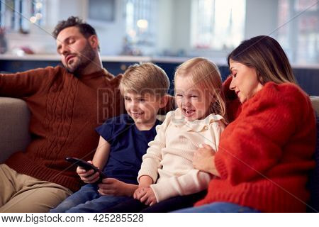Family Sitting On Sofa Watching TV Together As Parents Fall Asleep