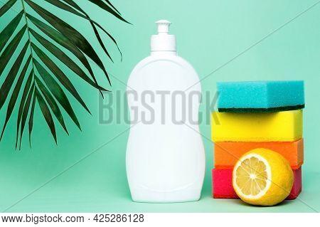 Bottle Of Dishwashing Liquid, Sponges And Lemon On Color Background.