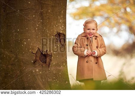 Portrait Of Young Girl Standing By Trunk Of Autumn Tree Playing Hide And Seek In Garden