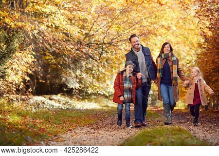 Family With Mature Parents And Two Children Holding Hands Walking Along Track In Autumn Countryside