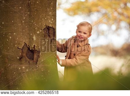 Young Girl Looking Around Trunk Of Autumn Tree Playing Hide And Seek In Garden