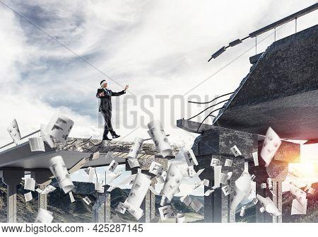 Businessman Walking Blindfolded Among Flying Documents On Concrete Bridge With Huge Gap As Symbol Of