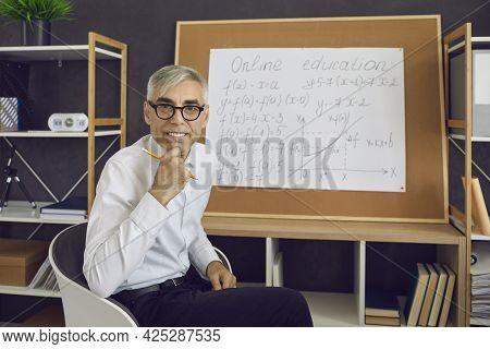 Portrait Of A Senior Positive Online Math Teacher Sitting At A Board With Math Formulas.