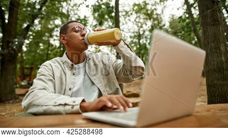 Selective Focus On Young African American Man Drinking Juice While Working On Laptop Outdoors, Wides