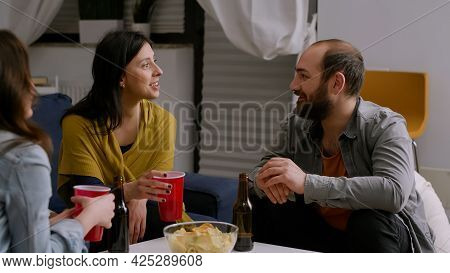 Multi-ethnic Friends Socializing During Night Home Party While Resting On Couch In Living Room Drink