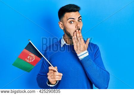 Young hispanic man with beard holding afghanistan flag covering mouth with hand, shocked and afraid for mistake. surprised expression