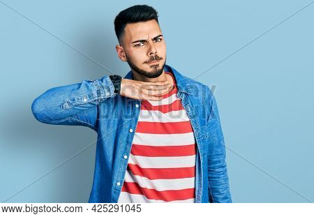 Young hispanic man with beard wearing casual denim jacket cutting throat with hand as knife, threaten aggression with furious violence