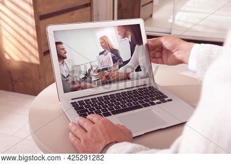 Man Attending Online Video Conference Via Modern Laptop At Table, Closeup