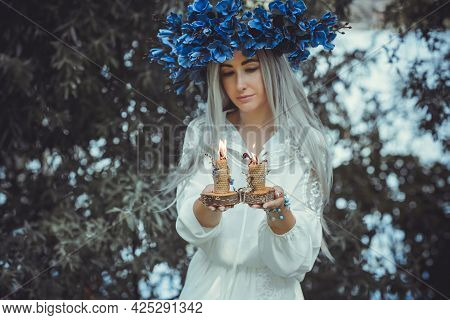 Beautiful Girl In Wreath Of Flowers In Forest. Portrait Of Young Beautiful Woman Wearing White Bride
