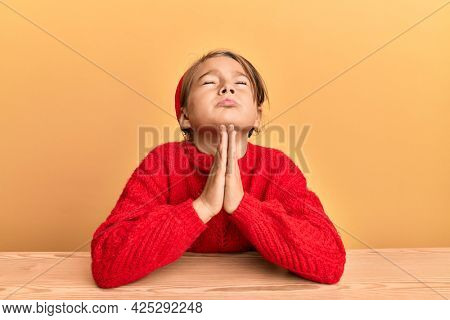 Little beautiful girl wearing casual clothes sitting on the table begging and praying with hands together with hope expression on face very emotional and worried. begging.