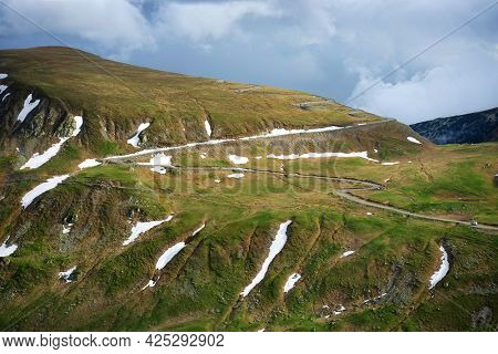 Beautiful scenic view in a rainy and cloudy day over the Transalpina road, the highest mountain road in the Carpathians located in the Parang mountains, Romania, Europe